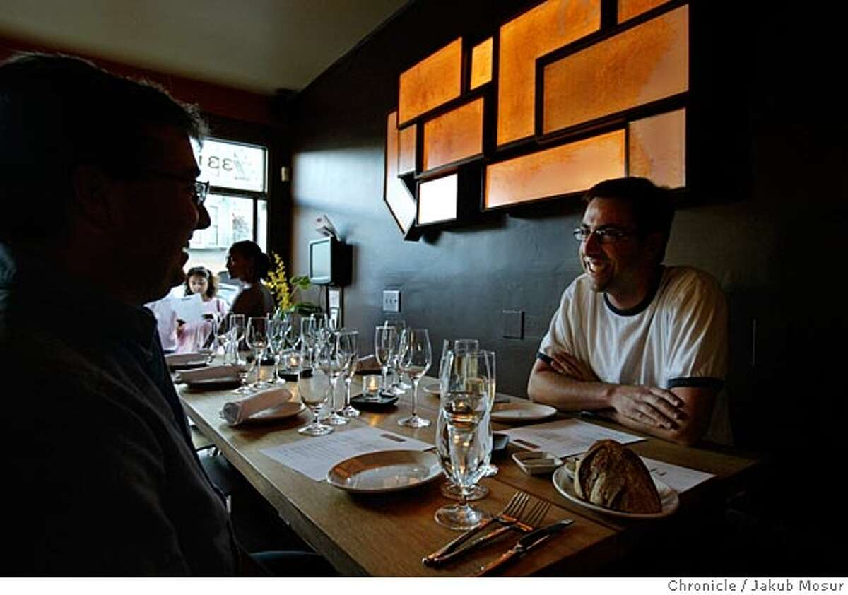 Jeremy Nichols and Karl Curtis talk before ordering their meal at Maverick, the American eatery and wine bar, in the Mission. Behind them hangs a backlit U.S. map created by Trey Gerfers, an artist from Point Reyes. Event on 7/15/05 in San Francisco. JAKUB MOSUR / The Chronicle