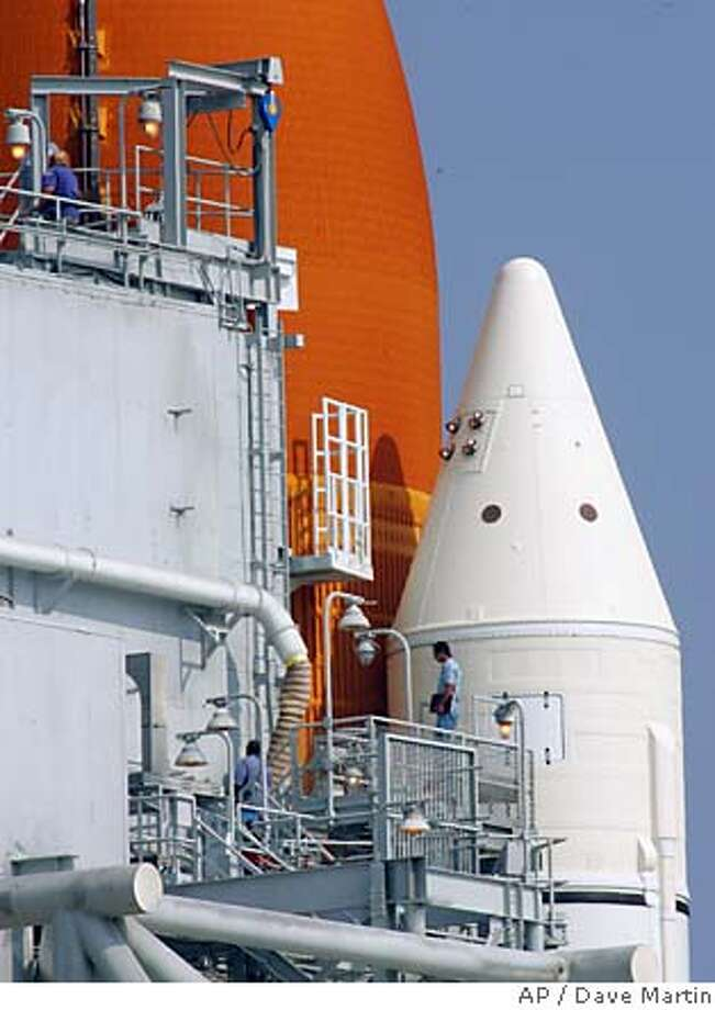 NASA workers continue preparations to the Discovery as it sits on Launch Pad 39B at the Kennedy Space Center in Cape Canaveral, Fla., Monday, July 24, 2005. Discovery is scheduled for launch on Tuesday. (AP Photo/Dave Martin) Photo: DAVE MARTIN