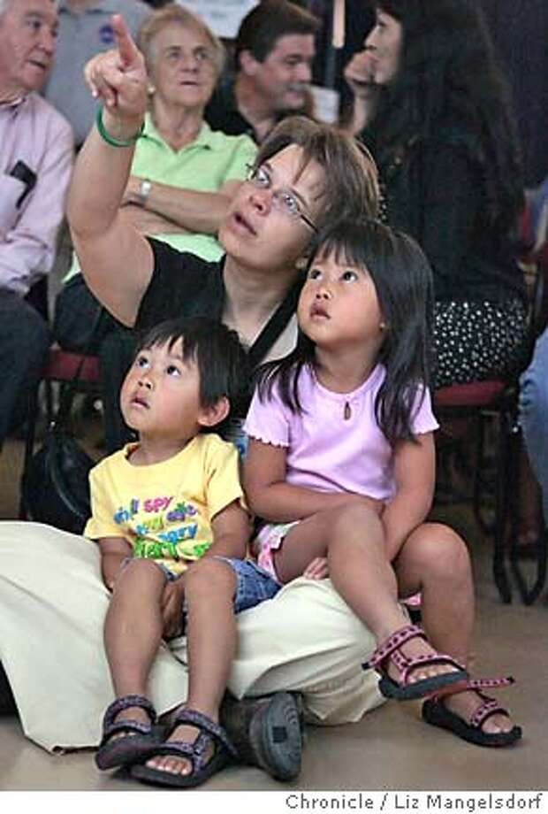 Event on 7/26/05 in Mountain View.  Nasa Ames employee Celeste Merryman watches the shuttle lift off with her children Quinn Wilmoth, 3, left and Tate Wilmoth, 4, right. They watch the shuttle launch at Nasa Ames Research Center. Nasa Ames employees and visitors watch the space shuttle launch Tuesday morning. Liz Mangelsdorf / The Chronicle Photo: Liz Mangelsdorf