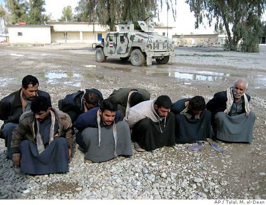 Detained men squat at an Iraqi army base in Baqouba, Iraq, 60 kilometers (35 miles) northeast of Baghdad, Wednesday Jan. 31, 2007. US military arrested some dozen man suspected of planning attacks on Shiite pilgrims during the Ashoura festivities and handed them over to the Iraqi authorities. (AP Photo/Talal. M. al-Dean)) Photo: TALA M. AL-DEAN