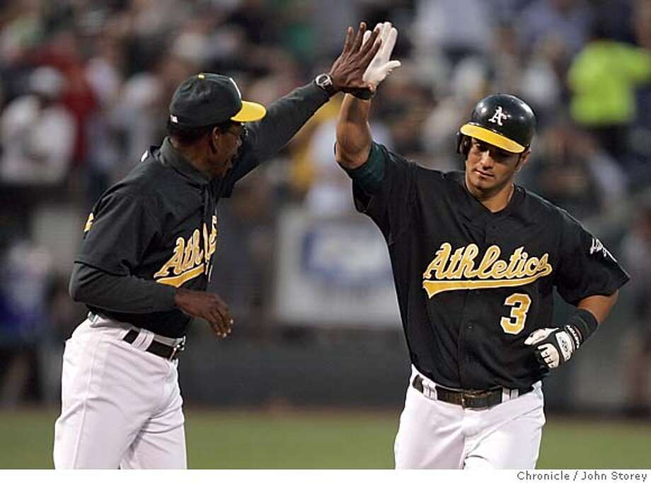 Athletics_jrs_0170.jpg  Eric Chavez of the A's gets a high five from 3rd base coach Ron Washington after his 4th inning home run. The Oakland Athletics vs. the Cleveland Indians at the McAfee  Coliseum. John Storey Oakland Event on 7/25/05  - MANDATORY CREDIT FOR PHOTOG AND SF CHRONICLE/ -MAGS OUT Photo: John Storey