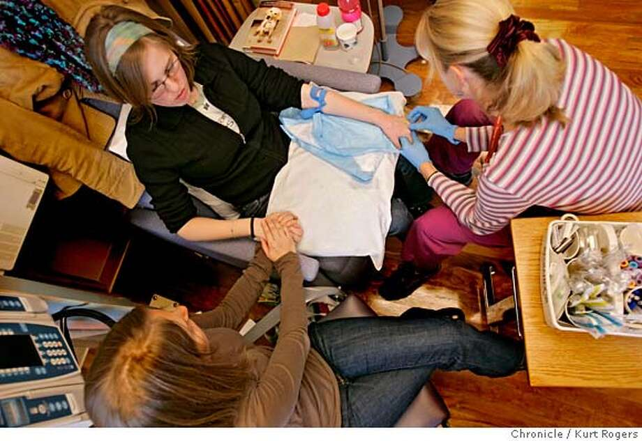Anja Manishin (right) inserts a needle into the back of Alicia Parlette's hand. An I.V. with her chemotherapy drug will be started and take about an hour to be fully absorbrd by her body. Kate Ferrogaiaro (cq) a life long friend of Alica's holds her hand.  Alicia Parlette is going through another round of chemotherapy.  FRIDAY, JANUARY 26, 2007 KURT ROGERS/THE CHRONICLE SAN FRANCISCO THE CHRONICLE  SFC ALICIA_0047_kr.jpg  Ran on: 02-02-2007  Nurse Anja Manishin (right) administers an IV as Kate Ferroggiaro (left) holds Alicia's hand. Photo: KURT ROGERS /THE CHRONICLE