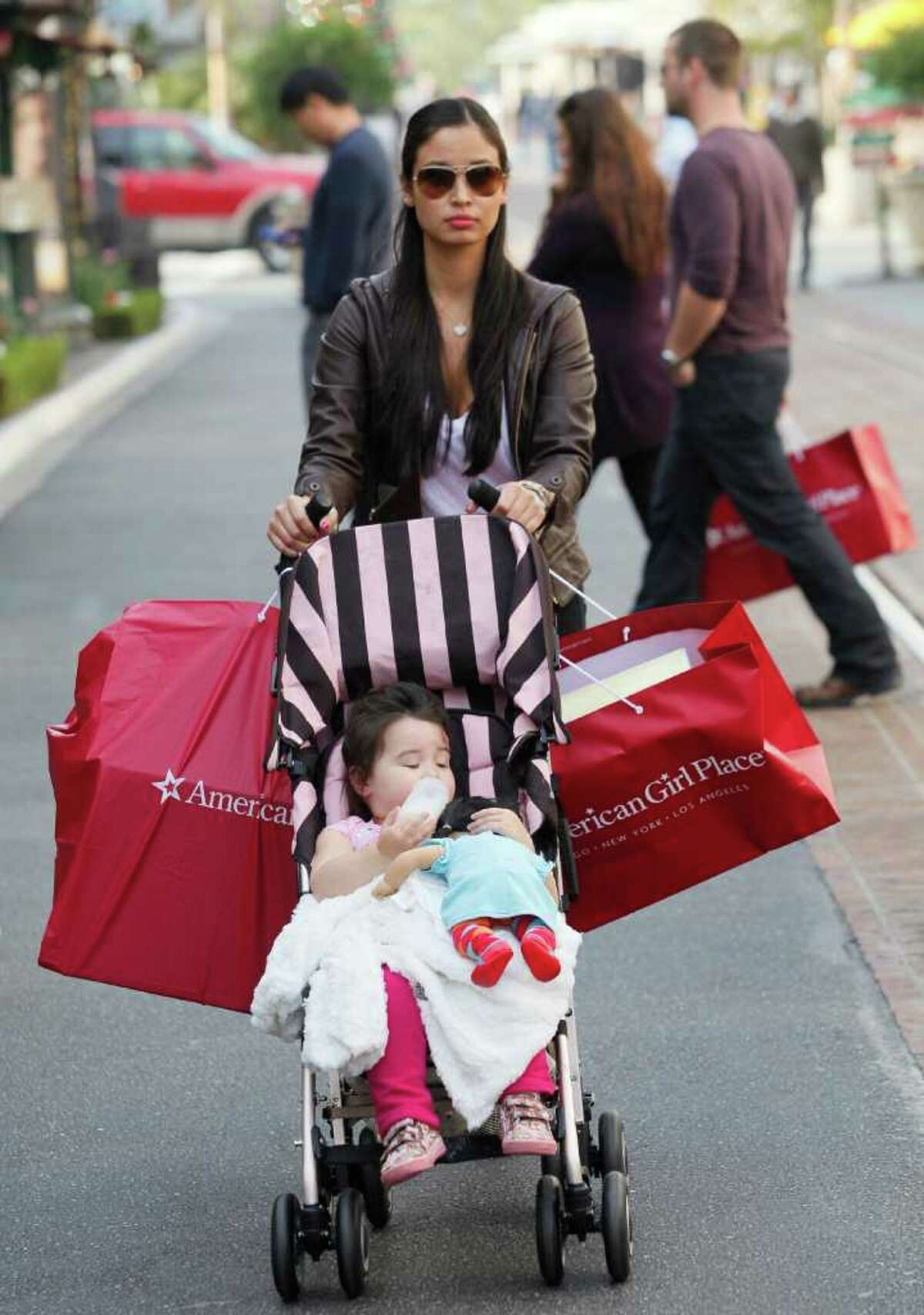 Shopper Monica Eaves, with her daughter, Sophia, 2, shops for holiday gifts at The Grove outdoor mall in Los Angeles on Tuesday, Dec. 14, 2010. A strong start to the holiday season is raising confidence that the consumer is back and that 2011 could be a better year for the economy than expected.