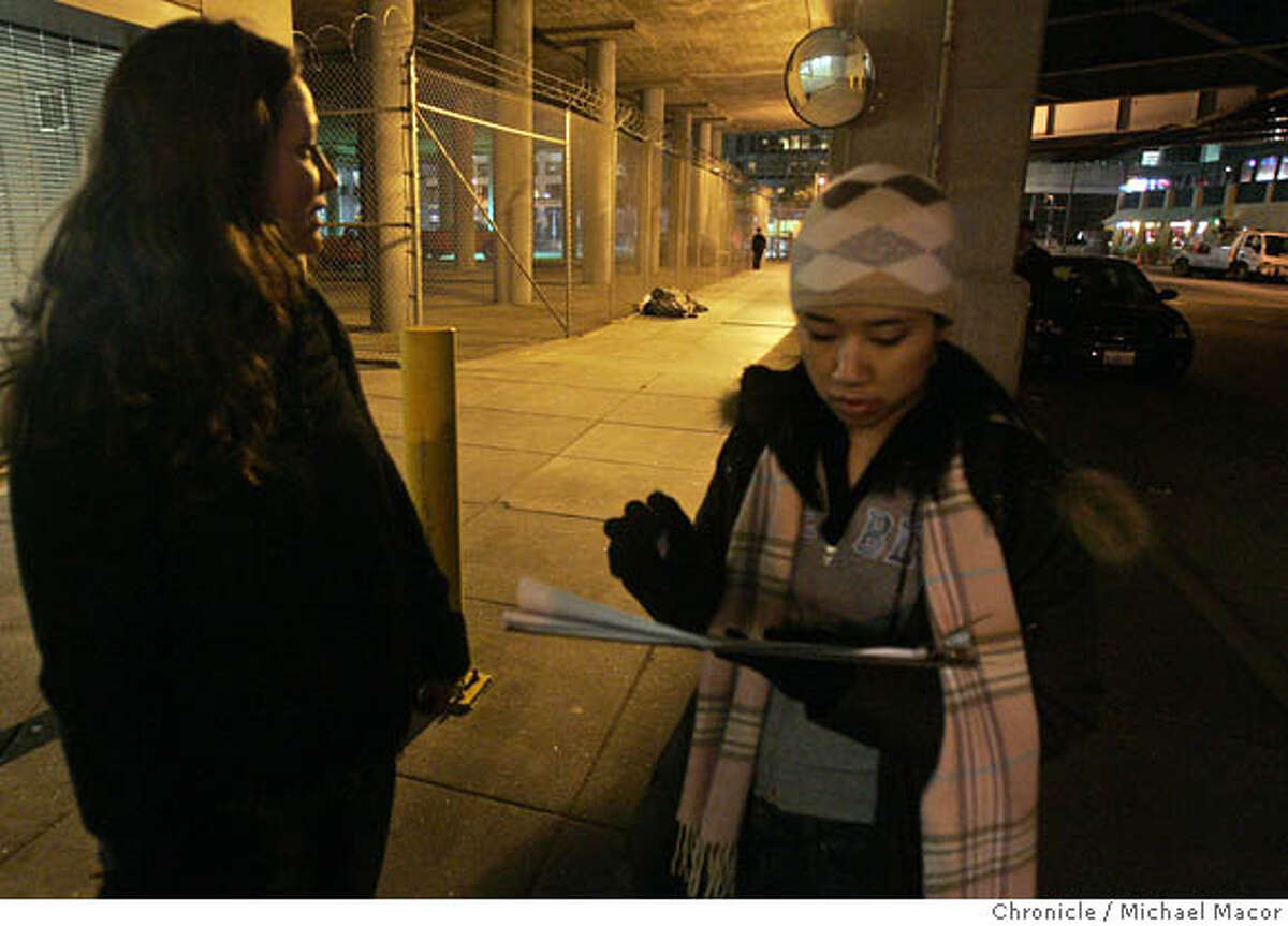 Volunteers Mary-Lynn Garrett, (left) and Laura Wong pass and record a group of homeless camped under the freeway overpass along Beale St. South of Market St. Staff from the City of San Francisco's Health and Human Services Agency, were joined by dozens of volunteers as they spread out across San Francisco this evening for the bi-annual homeless count. Photographed in, San Francisco, Ca, on 1/31/07. Photo by: Michael Macor/ San Francisco Chronicle