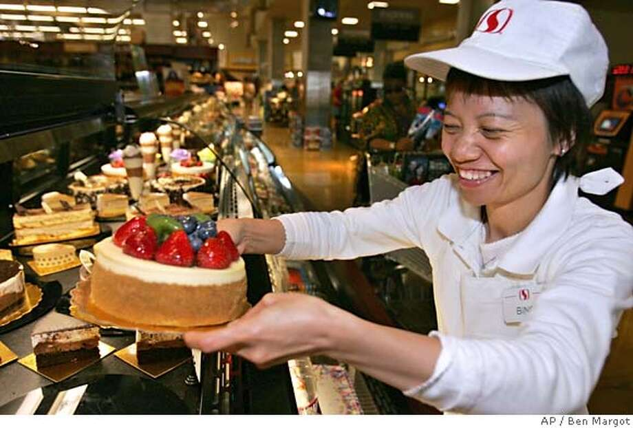 Safeway employee Bing Li places a dessert in a refrigerated display case at Safeway Monday, July 25, 2005, in San Francisco. Safeway Inc.'s second-quarter profit dropped 14 percent as higher gasoline prices and the costs of an ambitious makeover offset an uptick in sales at the big grocer. The Pleasanton-based company said Tuesday, July 26, 2005 that it earned $134 million, or 30 cents per share, during the three months ended June 18, down from $155.2 million, or 35 cents per share, at the same time last year. (AP Photo/Ben Margot) Photo: BEN MARGOT