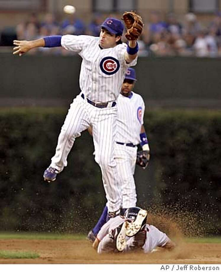 San Francisco Giants' Omar Vizquel, bottom, steals second as Chicago Cubs second baseman Todd Walker, top, leaps for the throw and shortstop Neifi Perez, rear, looks on during the third inning Monday, July 25, 2005 in Chicago. (AP Photo/Jeff Roberson) Photo: JEFF ROBERSON