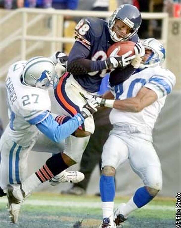 Chicago Bears wide receiver Marcus Robinson (88) pulls in a third-quarter 36-yard touchdown pass as he is caught between Detroit Lions' Mark Carrier, left, and Dwayne Harper, right, in Chicago, Sunday, Dec. 19, 1999. Chicago defeated Detroit 28-10. (AP Photo/Michael S. Green) Photo: MICHAEL S. GREEN