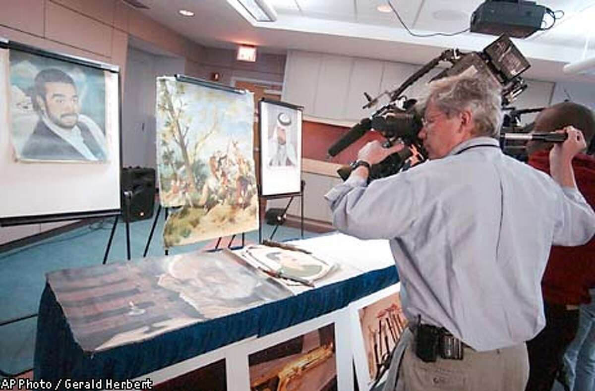 Members of the media gather around seized Iraqi artifacts during a news conference at the Bureau of Customs and Border Protection in Washington Wednesday, April 23, 2003. Several members of the media and a U.S. serviceman have been caught attempting to ship Iraqi paintings, weapons and other war souvenirs to America. At least 15 paintings, gold-plated firearms, ornamental knives, bonds and other items have been seized at airports in Washington, Boston and London in the last week. (AP Photo / Gerald Herbert)