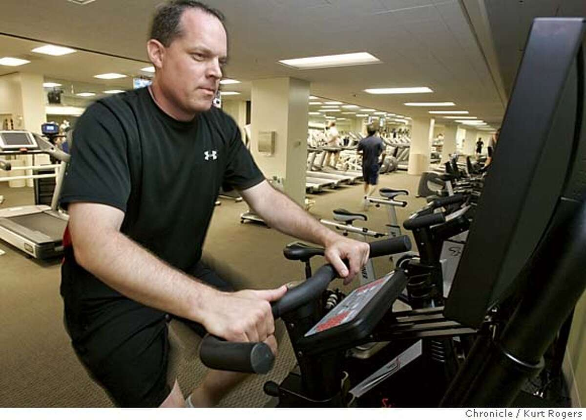 The latest development in the fitness world is a virtual reality exercise equipment that allows workout enthusiasts to simulate greats feats of athleticism � while riding a stationary bike. Brian Thomason who is a traner a the Bay Club under the BofA building on California St. rides the new bike. FITNESS18_0087_kr.JPG 7/12/05 in San Francisco,CA. KURT ROGERS/THE CHRONICLE MANDATORY CREDIT FOR PHOTOG AND SF CHRONICLE/ -MAGS OUT