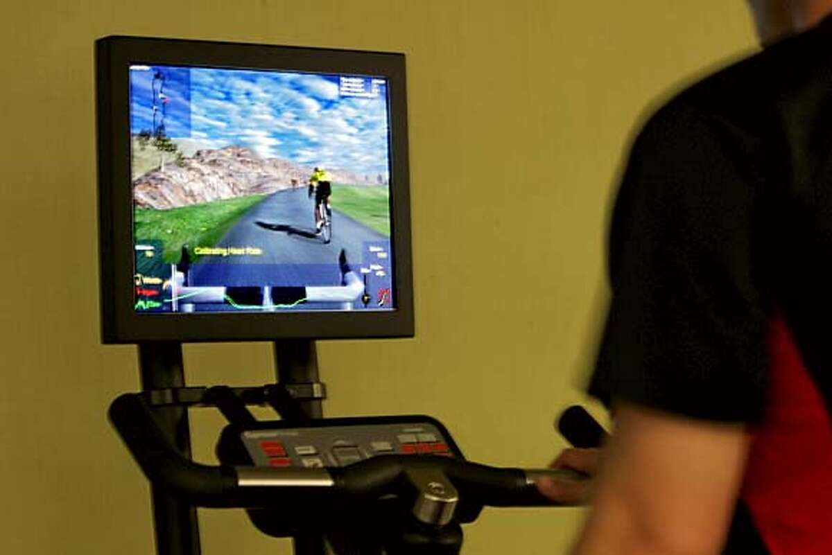 The latest development in the fitness world is a virtual reality exercise equipment that allows workout enthusiasts to simulate greats feats of athleticism � while riding a stationary bike. Brian Thomason who is a traner a the Bay Club under the BofA building on California St. rides the new bike. FITNESS18_0068_kr.JPG 7/12/05 in San Francisco,CA. KURT ROGERS/THE CHRONICLE MANDATORY CREDIT FOR PHOTOG AND SF CHRONICLE/ -MAGS OUT