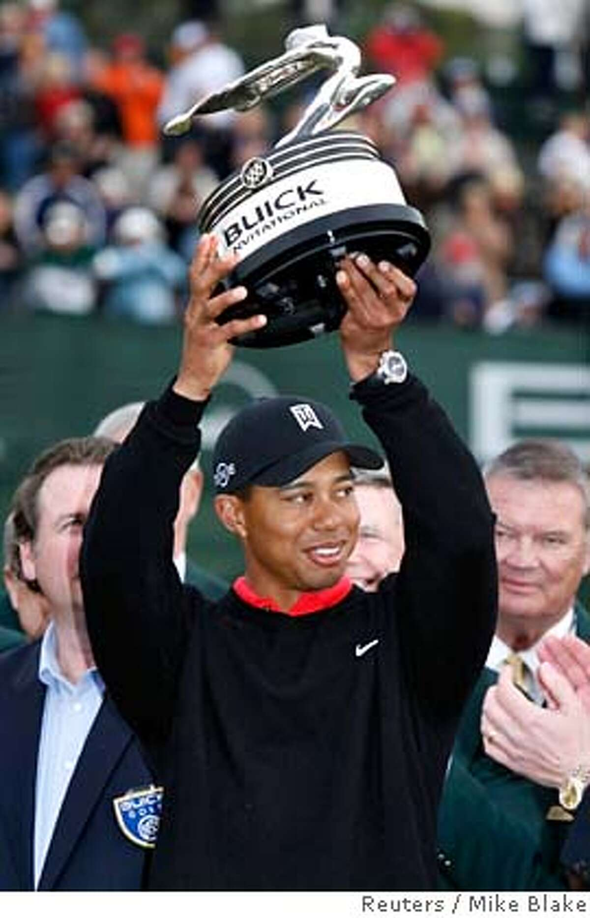 Tiger Woods holds up the trophy after winning the Buick Invitational golf tournament at Torrey Pines in La Jolla California January 28, 2007. Woods won his 7th consecutive PGA event with a final round 66 to finish 15-under par. REUTERS/Mike Blake(UNITED STATES)