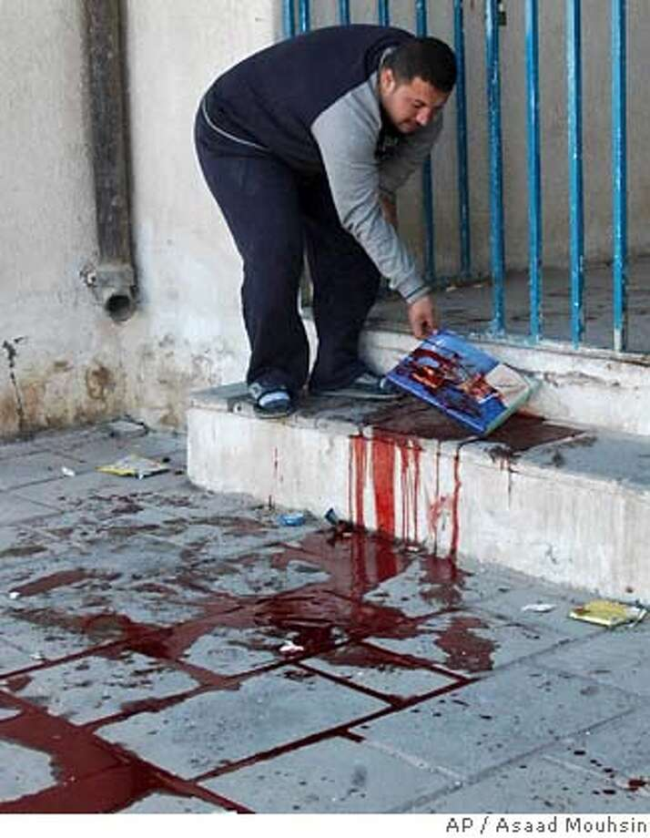 A man removes a bloodied schoolbook at a school gate in a mostly Sunni area of western Baghdad, Iraq, Sunday, Jan. 28, 2007. Mortar shells rained down Sunday on a girls secondary school killing five pupils and wounding 20, witnesses and police said. (AP Photo / Asaad Mouhsin) Photo: ASAAD MOUHSIN