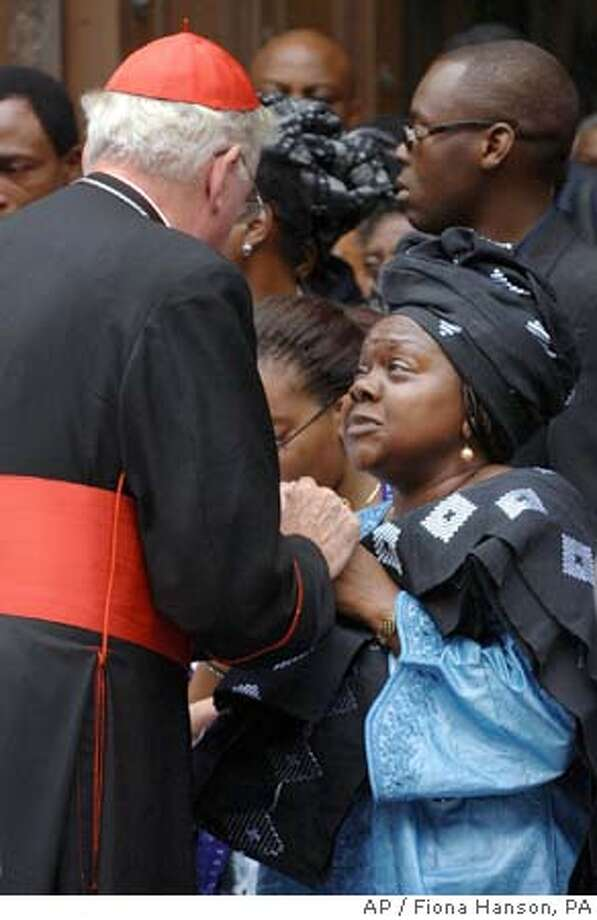 ** THIS IMAGE IS NOT POOL ** Marie Fatayi-Williams is comforted by Cardinal Cormac Murphy O'Connor after following the coffin of her son Anthony, 26, out of Westminster Cathedral, London, Saturday July 23, 2005, after a funeral mass was said for him following his death in a bomb explosion on the number 30 bus in Tavistock Square during the attacks of July 7. (AP Photo/ Fiona Hanson, PA) THIS IMAGE IS NOT POOL Photo: FIONA HANSON