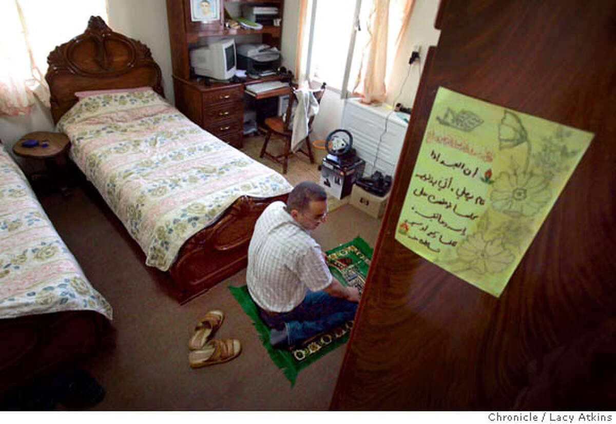 Khalad Salameh, who has his prayer hanging on his bedroom wall, prays before dinner at his home in Ramallah, June 20, 2005. He starts whatever he is doing and prays five times a day. Khalad Salameh, who works with computers for a Palestinian company in Ramallah , June 20, 2005. He was at home with mother Faheemeh and sister Rawa . Photographer Lacy Atkins