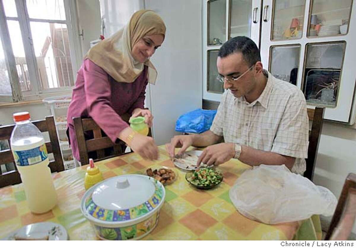 Faheemeh Salameh seasons her son Khalad Salameh's vegetable dish as he sits down for dinner at home in Ramallah, June 20, 2005. Khalad Salameh who works with computers for a Palestinian company in Ramallah , June 20, 2005. He was at home with mother Faheemeh and sister Rawa . Photographer Lacy Atkins
