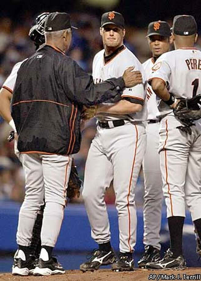 San Francisco Giants relief pitcher Jim Brower, center, gets a pat on the soulder from manager Felipe Alou as he is taken out of the game in the seventh inning, Sunday night, April 20, 2003, in Los Angeles. The Dodgers scored eight runs in the seventh inning. The Dodgers won the game 16-4. (AP Photo/Mark J. Terrill) Photo: MARK J. TERRILL