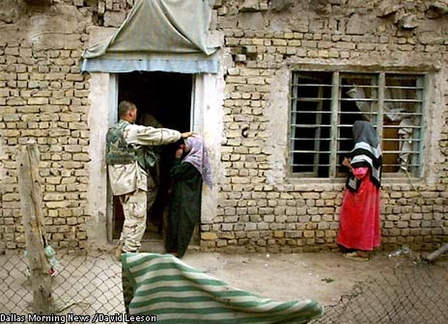 A soldier of the Task Force 2-69 Armor, 3rd Brigade Combat Team, 3rd Infantry Division from Fort Benning, Ga., touches the head of one of the sisters of Aii Hamid Sharif as another sister watches through the window, at their home near Baghdad, Saturday April 19, 2003. The child was burned from secondary explosions after an aerial attack on Iraqi military vehicles near her home. She was initially admitted to a hospital but was forced out when Iraqi soldiers took over the facility. Army medics found her in her village. They treated her and transported her to a local hospital. The hospital sent her back home, so Army medics decided to treat her there. (AP Photo/The Dallas Morning News, David Leeson) Photo: DAVID LEESON