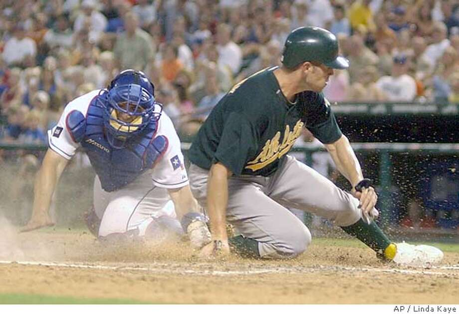 Texas Rangers' catcher Rod Barajas tries to tag Oakland Athlethics' Bobby Crosby as he slides across home plate safe in the fifth inning in Arlington, Texas, Friday, July 22, 2005. (AP Photo/Linda Kaye) Photo: LINDA KAYE/STR