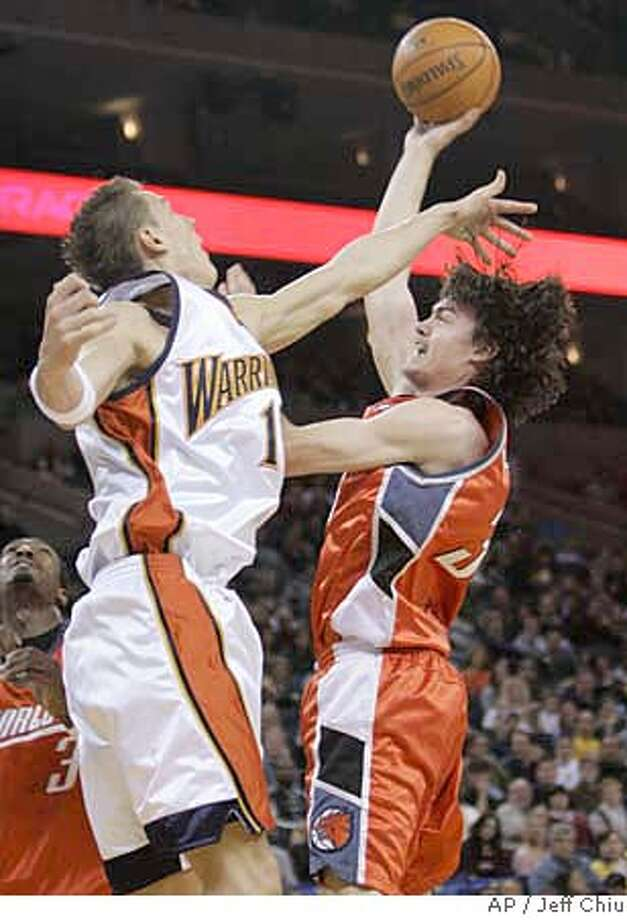 Charlotte Bobcats' Adam Morrison, right, attempts a shot as he is guarded by Golden State Warriors' Andris Biedrins, from Latvia, in the first quarter of an NBA basketball game in Oakland, Calif., Saturday, Jan. 27, 2007. (AP Photo/Jeff Chiu) Photo: Jeff Chiu