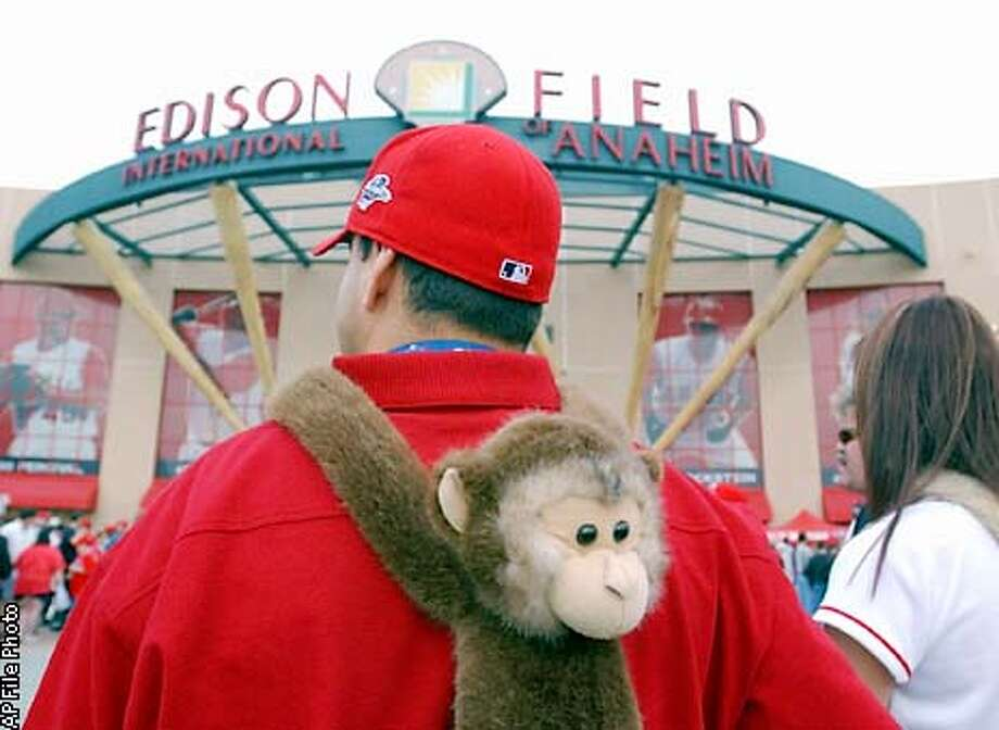 ** FILE ** Steve Moreno, of Orange, Calif., walks toward the entrance to Edison Field with a rally monkey on his back before Game 1 of the World Series between the Anaheim Angels and San Francisco Giants in Anaheim, Calif., Saturday, Oct. 19, 2002. Anaheim has put down the ThunderStix and rally monkeys and picked up the Fowl Towels and duck calls. Just like the Angels, their neighbors across the street, the Mighty Ducks have pulled off a playoff upset and raised the hopes of Southern California fans.(AP Photo/Julie Jacobson) Photo: JULIE JACOBSON