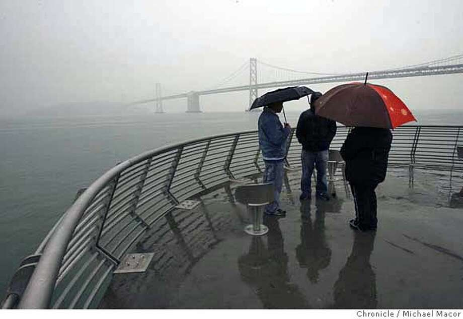 rain_097_mac.jpg l to r- Chris Marisol, Naaman Black and Edina Reyes spend their lunch break with a walk out on Pier 14 along the Embarcadero. Rain showers fell across the Bay Area today, the first rains in some time, there is a chance of rains continuing tomorrow. Photographed in, San Francisco, Ca, on 1/26/07. Photo by: Michael Macor/ San Francisco Chronicle Mandatory credit for Photographer and San Francisco Chronicle / Magazines Out Photo: Michael Macor