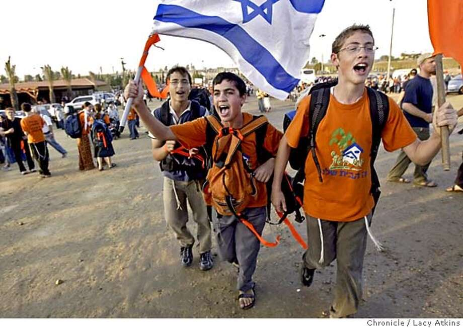 Chaim Alster, Elyshiv Cherlow and Noam Miller march up to the rally as thousands gather, Mondya July 18, 2005, in an anti-disengagement march. A two-kilometer-long column of tens of thousands of demonstrators marched out of Netivot , Monday July 18, 2005, but were stopped by a blockade of several hundred police and soldiers at the entrance to Kfar Maimon. The anti-disengagement march headed for Gush Katif from Netivot in the northern Negev started moving again towards Kfar Maimon after being stopped bodily Monday night at the entrance to the village by a barricade of security forces. Photographer Lacy Atkins Photo: LACY ATKINS