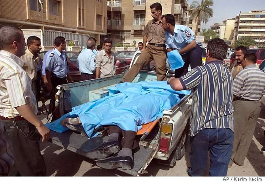 The bodies of Sunni Muslim National Dialogue Council member Iraqi Mijbil and two unidentified persons are loaded onto a police truck after being gunned down in the Karradah area of Baghdad, Iraq, Tuesday afternoon, July 19, 2005. Appointed to a committee to draft Iraq's constitution, Issa was leaving a committee meeting at Baghdad's Convention Center on the edge of the heavily fortified Green Zone, home to U.S. embassy and Iraqi government offices. (AP Photo/Karim Kadim) Photo: KARIM KADIM