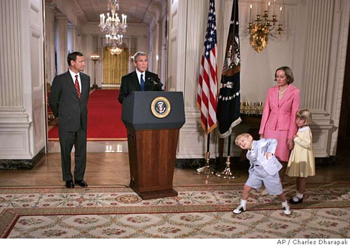 ** CAPTION ADDITION, ADDS AGES AND NICKNAMES OF CHILDREN ** President Bush introduces his nominee for the Supreme Court, John G. Roberts Jr., left, as his son John, (Jack), age 4, dances, and wife Jane and daughter Josephine, (Josie), age 5, look on in the State Dining Room at the White House, Tuesday, July 19, 2005, in Washington. President Bush chose federal appeals court judge John G. Roberts Jr. on Tuesday as his first nominee for the Supreme Court, selecting a rock solid conservative whose nomination could trigger a tumultuous battle over the direction of the nation's highest court. (AP Photo/Charles Dharapak) CHILDREN'S AGES ARE NOT KNOWN