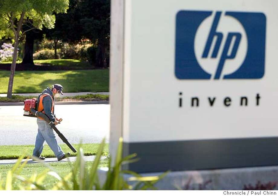 A groundskeeper cleans up the sidewalk in front of Hewlett Packard's corporate headquarters on 7/19/05 in Palo Alto, Calif. shortly after the company announced it's laying off up to 14,000 employees over the next year-and-a-half.  PAUL CHINN/The Chronicle Photo: PAUL CHINN