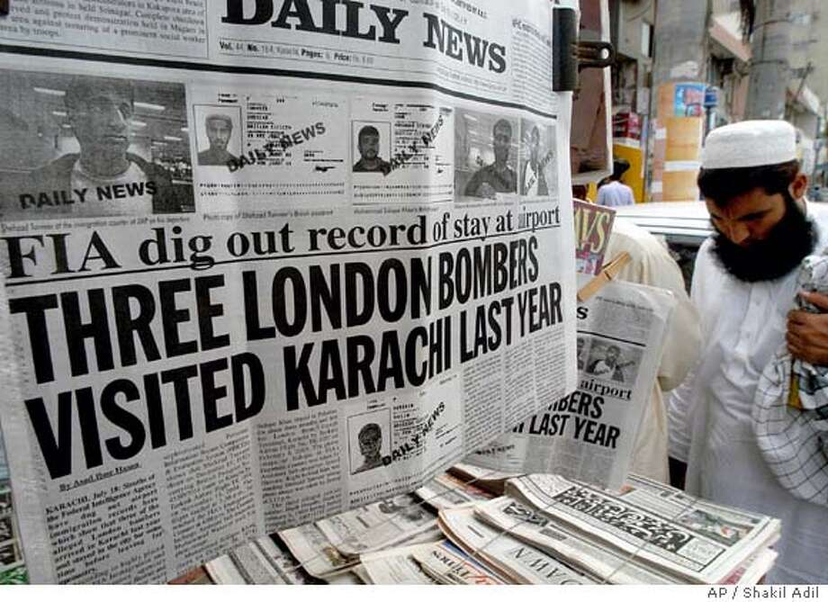 A Pakistani man reads an evening newspaper with the headline story of the three suspects of Londons suicide bombing, at a newspapers stall in Karachi, Pakistan on Monday, July 18, 2005. Three of the four suspected suicide bombers in the July 7 attacks in London traveled to Karachi in 2004, but the purpose of their visits was unclear, an immigration official said Monday. (AP Photo/Shakil Adil) Photo: SHAKIL ADIL