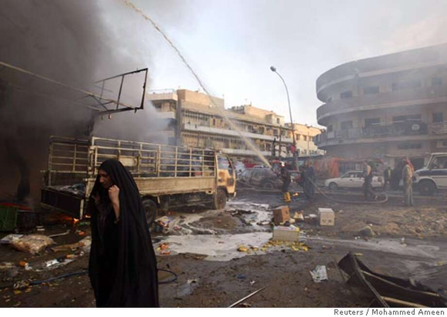 A woman walks past the scene of a car bomb attack in Baghdad January 25, 2007. The attack killed two people and wounded six others, police said. REUTERS/Mohammed Ameen (IRAQ)  Ran on: 01-26-2007  A car bomb attack in Baghdad killed two people and wounded six others, police said.  Ran on: 01-26-2007  This car bomb attack, one of several bombings in Baghdad, killed two people, police said. Photo: MOHAMMED AMEEN