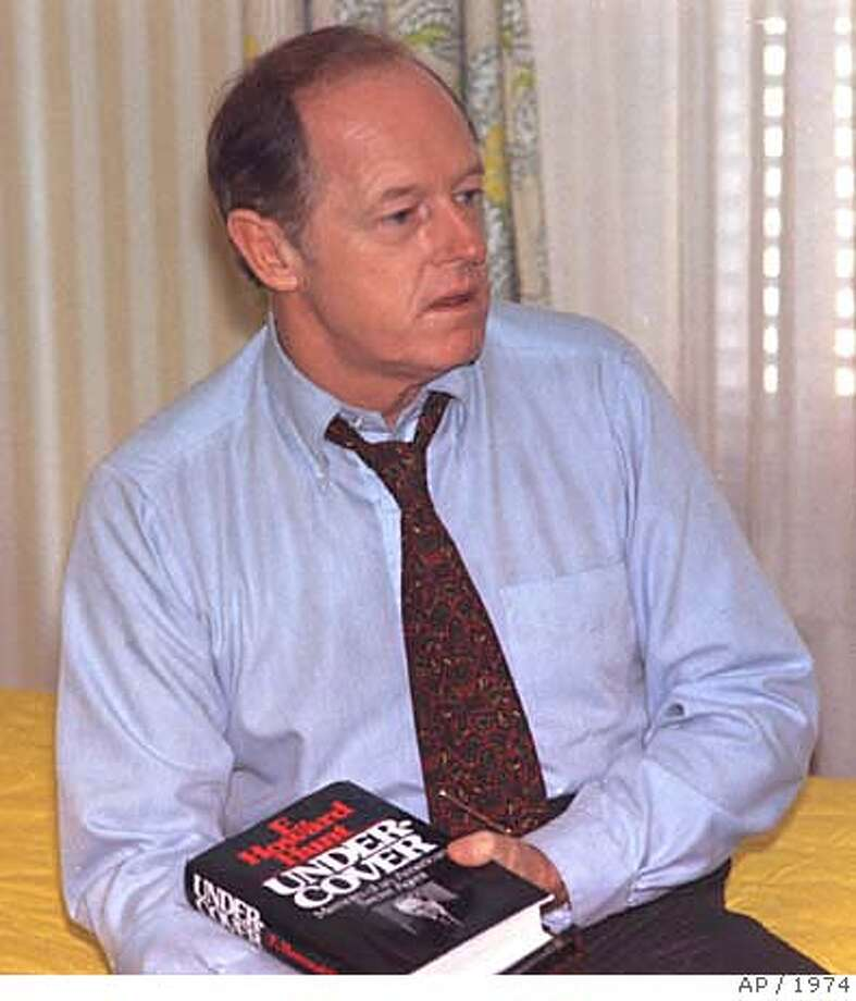 "** FILE ** E.Howard Hunt, holding a copy of his book ""Under Cover"" is seen in this Nov. 15,1974 file photo at an unknown location. Hunt, who helped organize the Watergate break-in that led to the greatest scandal in American political history and the downfall of Richard Nixon's presidency, died Tuesday, Jan 23, 2007. He was 88. (AP Photo) NOV. 15,1974 FILE PHOTO Photo: AP Photo"