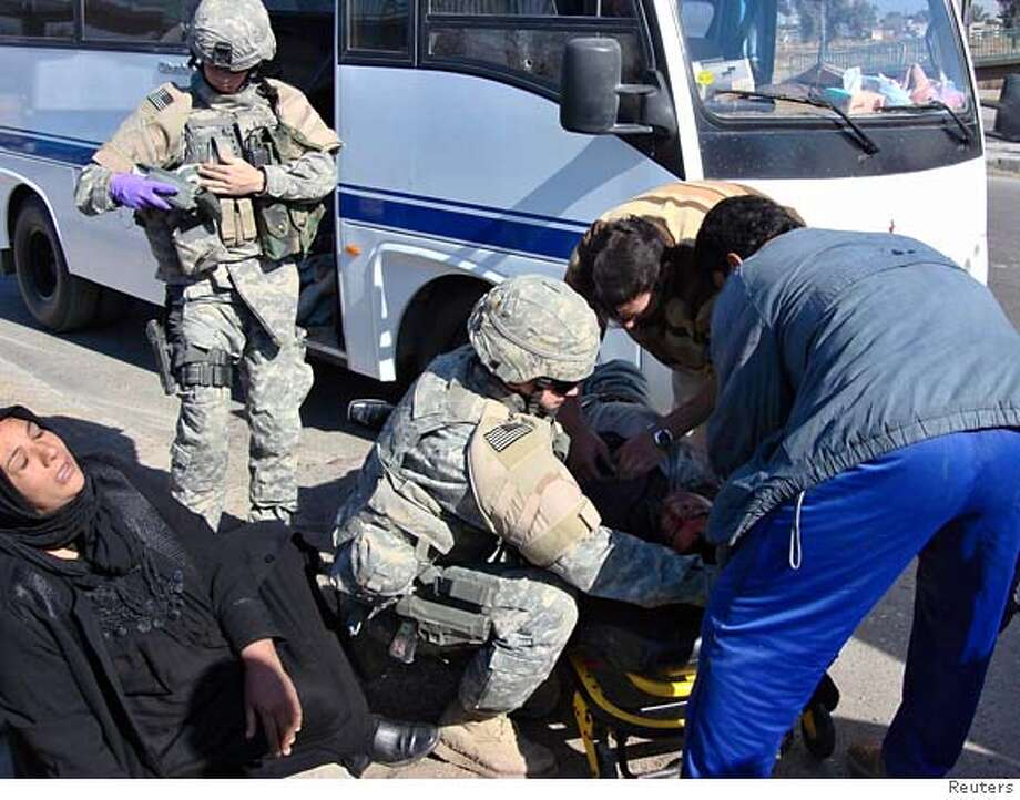 Residents and a U.S. soldier help an injured pilgrim after an attack by gunmen in Baghdad January 24, 2007. Gunmen opened fire on a minibus carrying Shi'ite pilgrims and wounded two of them in the southern Saydiya district of Baghdad, police said. REUTERS/Stringer (IRAQ) 0 Photo: STRINGER/IRAQ