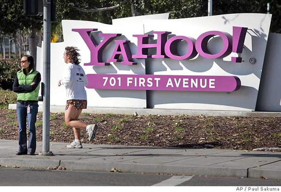 The entrance sign of Yahoo! headquarters stands as people pass in Sunnyvale, Calif., Monday, Jan. 22, 2007. Yahoo Inc. is expected to report earnings for the fourth quarter and fiscal year 2006 after the market closes. (AP Photo/Paul Sakuma) Photo: PAUL SAKUMA