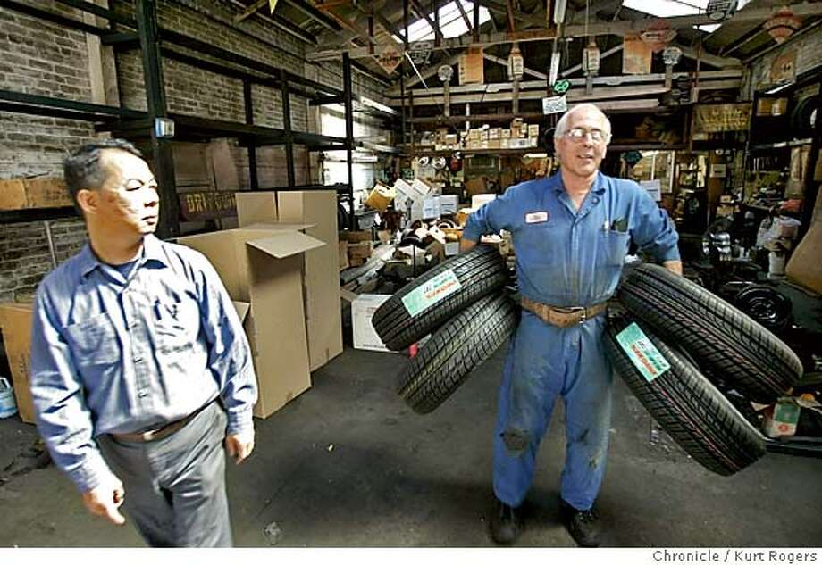 Tony Fung watches as John Rivelli takes some tire's as they are busy cleaning out their property.  Tony Fung owner of Autohouse and John Rivelli the owner of Rivelli Tire .Both businesses are being evicted using domain to pave the way for a giant housing complex.  EVICT02_0119_kr.JPG 7/1/05 in Oakland,CA.  KURT ROGERS/THE CHRONICLE Ran on: 07-02-2005  Tony Fung watches John Revelli carry inventory away from Revelli Tire, next to Fung's Autohouse. Both businesses are being evicted. MANDATORY CREDIT FOR PHOTOG AND SF CHRONICLE/ -MAGS OUT Photo: KURT ROGERS