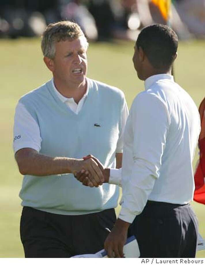 Scotland's Colin Montgomerie, left, and Tiger Woods of the United States shake hands at the end of the 3rd round of the British Open golf championship on the Old Course at St. Andrews, Scotland Saturday July 16, 2005. (AP Photo/Laurent Rebours) EDITORIAL USE ONLY Photo: LAURENT REBOURS