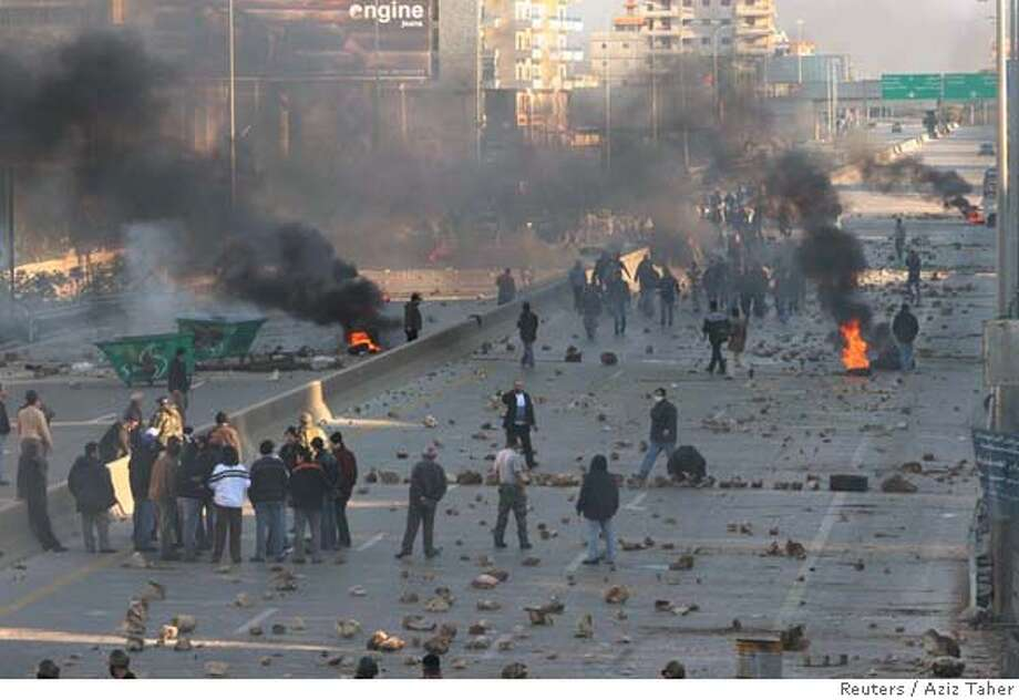 Protesters block a street with burning tyres on a road leading to south Lebanon at the start of a general strike called by the opposition in Khaldeh, south of Beirut January 23, 2007. Thousands of Lebanese protesters blocked main roads in Beirut and around the country with rubble and burning tyres on Tuesday at the start of a general strike called by the opposition to try to topple the government. REUTERS/Aziz Taher (LEBANON) 0 Photo: STR