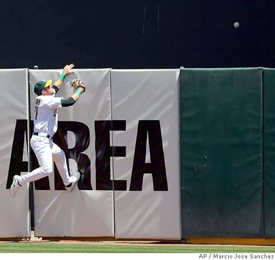 Oakland Athletics center fielder Mark Kotsay, left, leaps at the wall as a line drive by the Texas Rangers' Hank Blalock goes over the fence for a solo home run in the first inning on Saturday, July 16, 2005. Texas won 10-8. (AP Photo/Marcio Jose Sanchez) Photo: MARCIO JOSE SANCHEZ