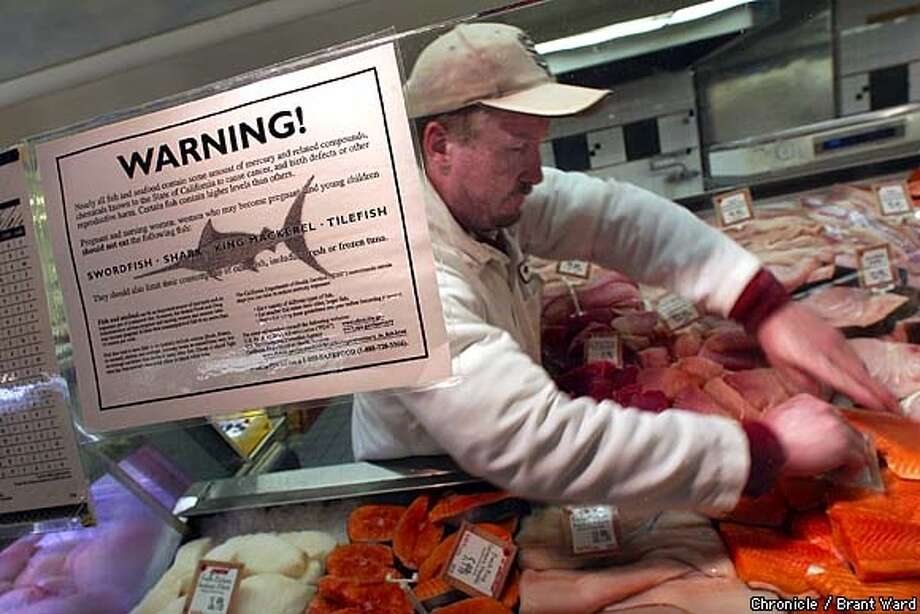 Andronico's Market seafood specialist Jamie O'Rourke does his magic in back of a large sign warning about the mercury levels of various species of fish. This market on Irving Street in San Francisco. By Brant Ward/Chronicle Photo: BRANT WARD