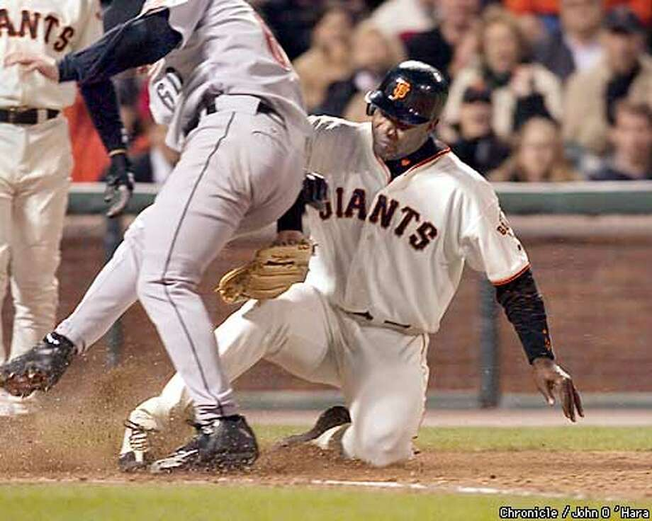 GIANTS-C-15APR03-SP-  PAC BELL LPARK, SAN FRANCISCO,CA  GIANTS V/S ASTROS  Bonds slide at home plate on wild pitch by pitcher Jeriome Robertson. Jose Cruz jr. also scored. Robertson tried to block the plate as Bonds slid.  PHOTO/JOHN O'HARA Photo: JOHN O'HARA