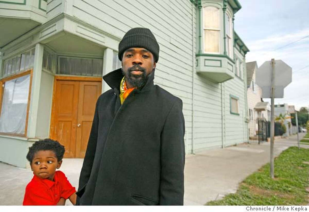"""�villagebottoms00291_mk.JPG with his son Diji Diallo, 5, in town, Marcel Diallo stands in front of a property he will be opening soon called """"Soul Foods Coop."""" West Oakland entrepreneur, Marcel Diallo,34, is racing against the gentrification clock to create an enclave of all things African-American in his neighborhood. He has a plan to create more black homeowners, black-owned cafes, galleries, boutiques and mom-and-pop shops. His vision is to call his West Oakland Neighborhood the Village Bottoms Cultural District. Mike Kepka / The Chronicle Marcel Diallo (cq) the source MANDATORY CREDIT FOR PHOTOG AND SF CHRONICLE/ -MAGS OUT"""