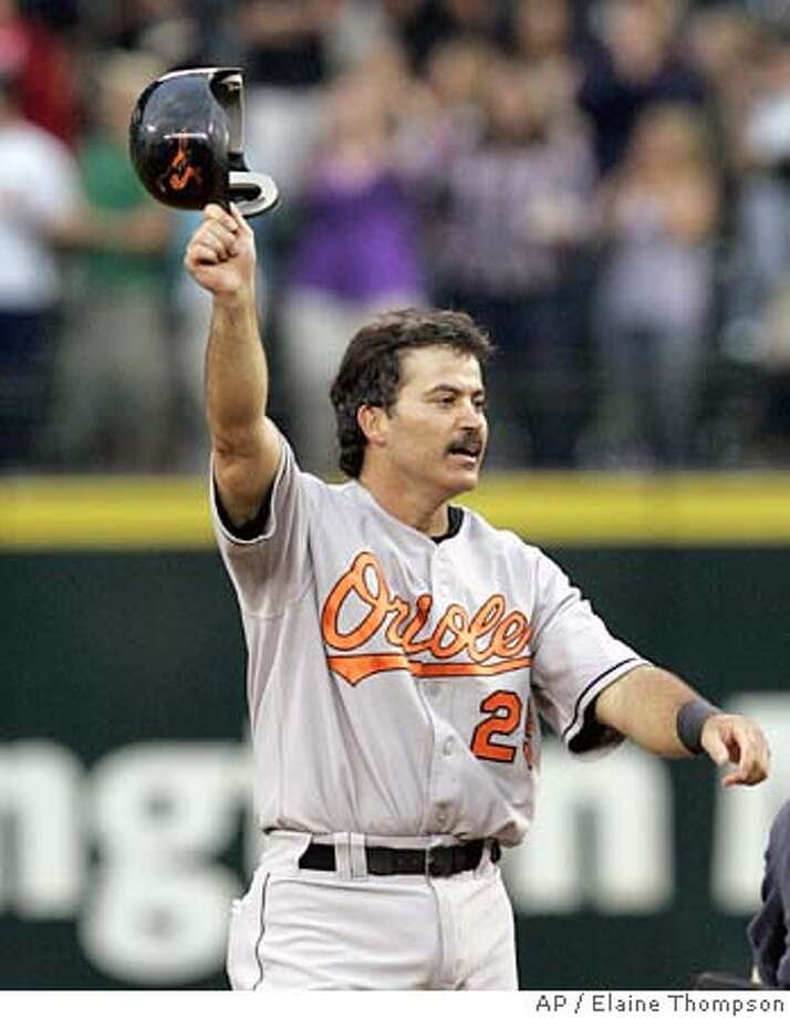 Baltimore Orioles' Rafael Palmeiro tips his batting helmet to the crowd after hitting a double against the Seattle Mariners in the fifth inning, Friday, July 15, 2005, in Seattle. Palmeiro's hit was the 3,000th of his career. (AP Photo/Elaine Thompson) Photo: ELAINE THOMPSON