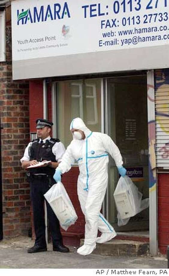 A forensic police officer carries computer equipment out of a building in Lodge Lane, Leeds, England Friday July 15, 2005, a short distance from the home of one of the suspected London suicide bombers. Two officers in protective suits and masks carried out bags clearly containing computer devices from the property in the Beeston area of Leeds. The building in Lodge Lane is near the home of Shehzad Tanweer, who is suspected to have killed seven people in the Aldgate blast in London last week. (AP Photo/ Matthew Fearn, PA) ** UNITED KINGDOM OUT ** Photo: MATTHEW FEARN