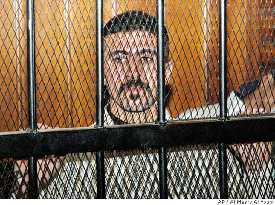 Egyptian mini-bus driver, Emad el-Kabir, 21, whom police sodomized, filmed his torture and transmitted it to the cell phones of the victim's friends in order to humiliate him, looks on behind the bars inside a courtroom on Tuesday, Jan. 9, 2007 in Cairo, where he was sentenced to three months in prison for `resisting authorities.' (AP Photo/Al Masry Al Youm) Photo: AL MASRY AL YOUM