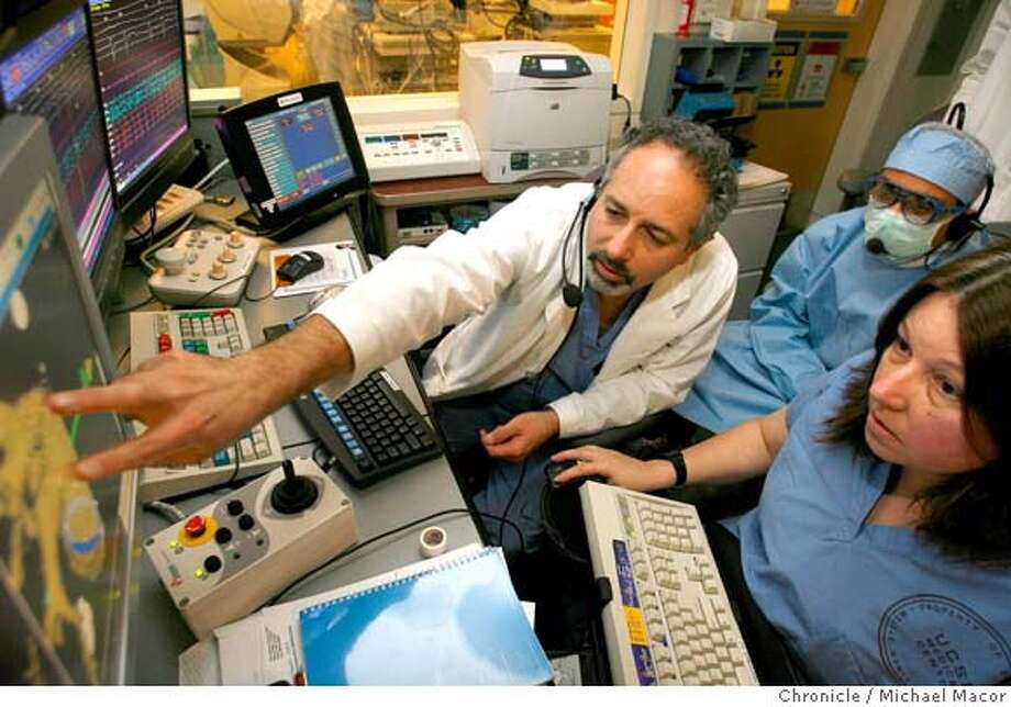 �lifescience1-21-2007_0052_mac.jpg The remote team, Dr. Jeffrey Olgin, (left) Chairman/Chief Electro Physiologist, Mohan Viswanathan,(center,) Electro Physiology Fellow and Donna Eustice, (right), Associate Developement Engineer, begin the mapping process of the patients heart. UCSF Medical Center is using a new robotic magnet to treat heart patients with Atrial Fibrillation. They had to knock out walls and rebuild a surgical room to fit these machines which sit on both sides of the operating table with the patient in-between. It is operated by remote control in a booth outside operating room with big screens to see the action. We will watch a patient undergo treatment by Dr. Jeffrey Olgin. Event in, San Francisco, Mo, on 11/29/06. Photo by: Michael Macor/ San Francisco Chronicle Mandatory credit for Photographer and San Francisco Chronicle / Magazines Out Photo: Michael Macor