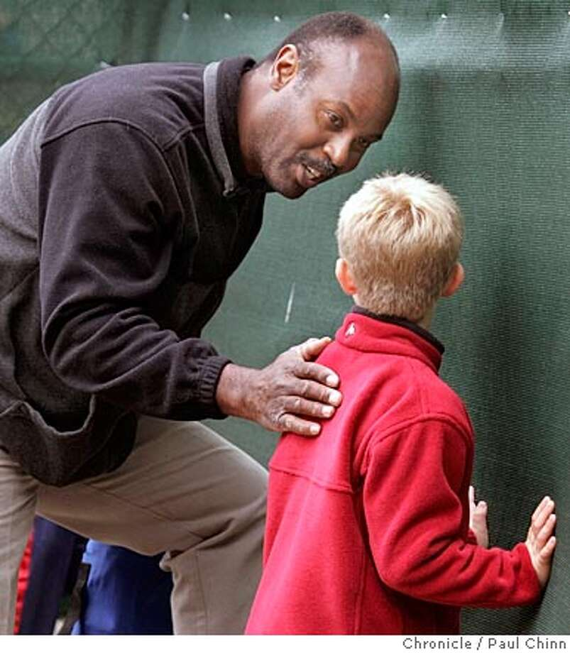 Terry Whitfield speaks to young baseball fan Brice Nelson, 8, of Burlingame, during the Hillsborough Little League All-Stars vs. Half Moon Bay game in the District 52 tournament on 7/9/05 in Pacifica, Calif. Former Giants player Terry Whitfield has been working as a batting coach for the Hillsborough little league team.  PAUL CHINN/The Chronicle Photo: PAUL CHINN