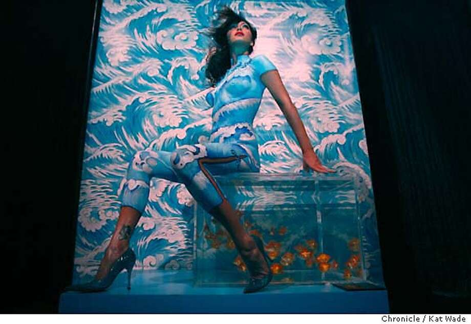 "MAC28_0142_KW_.jpg  Model Lee McCurdy, ""Wave"" sits on an aquarium filled with live goldfish in the Dome at the Westfield Mall , MAC cosmetic artists show off their models dressed in nothing but body paint designed to look like Chinese chengsom dresses on Thursday January 18, 2006. NOT PICTURED: Designer Nadine Luke, lead makeup artist Amna Pervez, makeup artists Cawsey Williams and Maranda James, headdress by Stephen Jones.  Kat Wade/The Chronicle Mandatory Credit for San Francisco Chronicle and photographer, Kat Wade, Mags out Photo: Kat Wade"