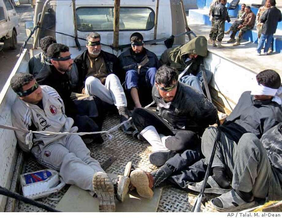 Blindfolded terrorist suspects sit in the back of a truck in Muqdadiyah about 90 kilometers (60 miles) north of Baghdad, Saturday, Jan. 20, 2007. 24 people were detained in a joint US and Iraqi army raid that also captured weapons and bomb making materials. (AP Photo/Talal. M. al-Dean)) Photo: TALA M. AL-DEAN