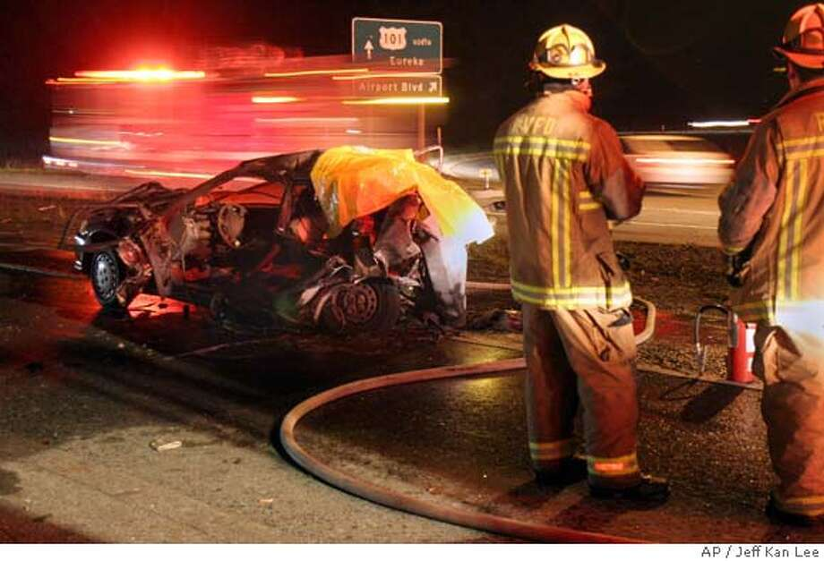 Rincon Valley firefighters look at a car involved in a fatal accident that burned on Highway 101 north of the Airport Boulevard overpass, north of Santa Rosa, Calif., on Friday, Jan. 19, 2007. (AP Photo/Press Democrat, Jeff Kan Lee) Photo: Jeff Kan Lee