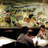 Patrons enjoy dinner beneath one of many paintings in the dining room at Tamarine restaurant in Palo Alto, Ca.  (BY CARLOS AVILA GONZALEZ/THE SAN FRANCISCO CHRONICLE)